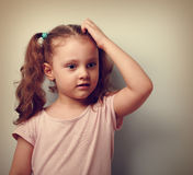 Cute thinking worried kid girl sctaching the head and looking. V Stock Images