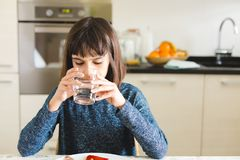 Cute thirsty girl drinking water in a glass at home Stock Photography