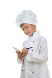 Cute boy chef writes down a recipe into a notebook, on white background. Royalty Free Stock Photography
