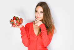 Cute thoughtful brunette with strawberries. Royalty Free Stock Images