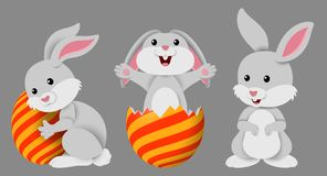 Cute three little bunnies with decorated Easter eggs on a gray background royalty free illustration