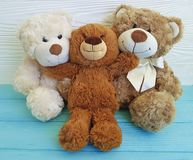 Cute three teddy bear toy with red box on colored wooden, family Stock Photos
