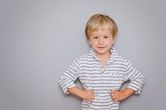 Cute three years old boy with blond hair on grey background with copy space. Cute three years old boy woth blond hair on grey background with copy space stock image
