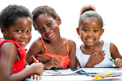 Cute threesome African girls drawing together. Stock Photos