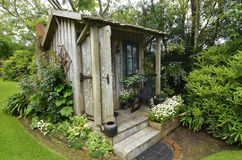 Cute tiny timber antique shack sitting in stunning flower garden royalty free stock images