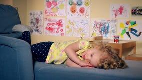 Cute tired girl sleeping on sofa stock video footage