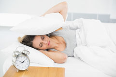 Cute tired woman covering her ears with pillows. Lying on her bed Stock Image