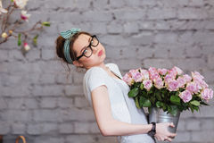 Cute tired young woman holding heavy bucket with pink roses Stock Image