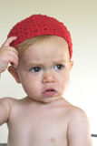 Cute Toddler. Image of cute toddler wearing a crochet cap, scratching his head Royalty Free Stock Images