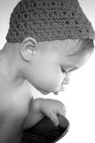 Cute Toddler. Black and white image of cute toddler wearing a crochet cap, looking over the side of a galvanized tub Stock Image