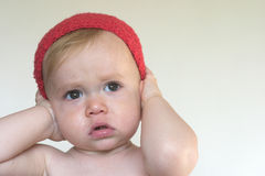 Cute Toddler. Image of cute toddler holding his hands over his ears Stock Photo