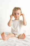Cute toddler. Sitting and pulling on his ears Stock Images