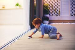 Cute toddler baby boy playing with toy car at the patio with open space kitchen and sliding doors. Cute toddler, baby boy playing with toy car at the patio with royalty free stock photos