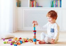 Cute toddler baby boy playing with wooden blocks, building a balancing high tower stock photography
