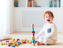 Cute toddler baby boy playing with wooden blocks, building a high tower stock photo