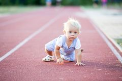 Cute toddler baby boy on a running path on a stadium. Playing royalty free stock images