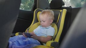 Cute toddler baby boy sitting in car seat and watching a video from smart-phone. Kid playing in the car with smartphone. Technology and internet addiction stock video