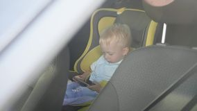 Cute toddler baby boy sitting in car seat and watching a video from smart-phone. Kid playing in the car with smartphone. Technology and internet addiction stock footage