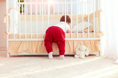 Cute toddler baby climbing into the cot in nursery room at home. Cute toddler baby boy climbing into the cot in nursery room at home Royalty Free Stock Photos