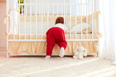 Cute toddler baby climbing into the cot in nursery room at home. Cute toddler baby boy climbing into the cot in nursery room at home stock photo