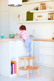 Cute toddler baby climbs on step stool, trying to reach things on the high desk in the kitchen Royalty Free Stock Photography