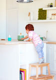 Cute toddler baby climbs on step stool, trying to reach things on the high desk in the kitchen Stock Photography
