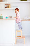 Cute toddler baby climbs on step stool, trying to reach things on the high desk on the kitchen. Cute toddler baby boy climbs on step stool, trying to reach stock photography