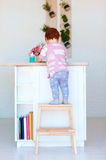 Cute toddler baby climbs on step stool, trying to reach things on the high desk in the kitchen Stock Images