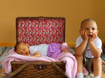 Cute toddler and Baby girl. Cute little boy sitting discontent next to baby girl sleeping in a basket Stock Photography