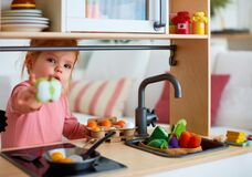 Free Cute Toddler Baby Girl Playing On Toy Kitchen At Home, Roasting Eggs And Treat You With Apple Slice, Let`s Share Stock Photography - 210896452