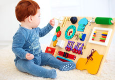 Cute toddler baby playing with busy board at home Royalty Free Stock Photo