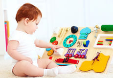 Cute toddler baby playing with busy board at home Royalty Free Stock Photos