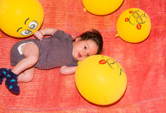 Cute toddler baby resting on the ground with yellow balloons Royalty Free Stock Photo