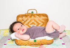 Cute toddler baby resting in the small wooden travel suitcase Stock Photo
