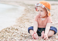 Cute toddler baby  sitting on the beach Stock Image