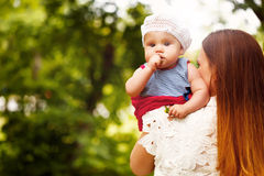 Cute Toddler Baby sitting on Mom`s Hands Royalty Free Stock Photo