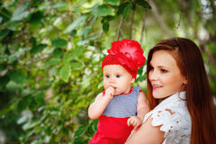 Cute Toddler Baby sitting on Mom`s Hands Stock Photo