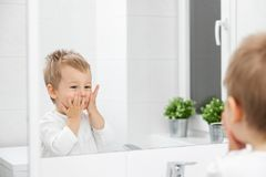 Cute toddler learning how to wash his face. Cute toddler in the bathroom mirror learning how to wash his face Stock Photos