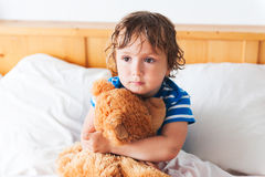 Cute toddler in a bed. Cute toddler boy resting in a bed with teddy bear Stock Photography