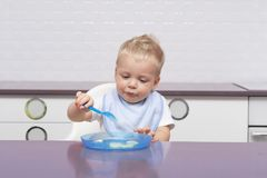 Cute toddler in a blue bib eating banana in the modern kitchen.  Stock Photo