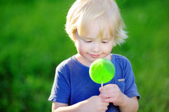 Cute toddler boy with big green lollipop Stock Photo