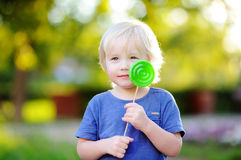 Cute toddler boy with big green lollipop Stock Photography