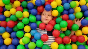 Cute toddler boy, child, playing in colorful balls in children playground, view from aboeve stock video