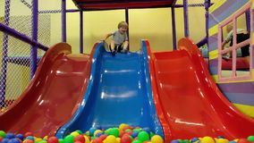 Cute toddler boy, child, riding on the hill in colorful balls in children playground, indoors stock video