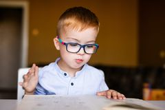 Cute toddler boy with down syndrome with big glasses reading intesting book royalty free stock photos