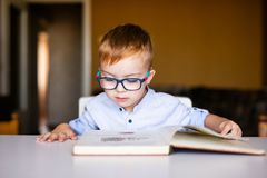 Cute toddler boy with down syndrome with big glasses reading intesting book stock image