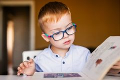 Cute toddler boy with down syndrome with big glasses reading intesting book stock images