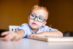 Cute toddler boy with down syndrome with big glasses reading intesting book royalty free stock photo