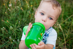 Cute toddler boy drinking Royalty Free Stock Images