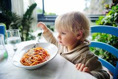 Cute toddler boy eating pasta in indoors restaurant. Cute toddler boy eating pasta in Italian indoors restaurant. Healthy/unhealthy food for little kids Royalty Free Stock Photo